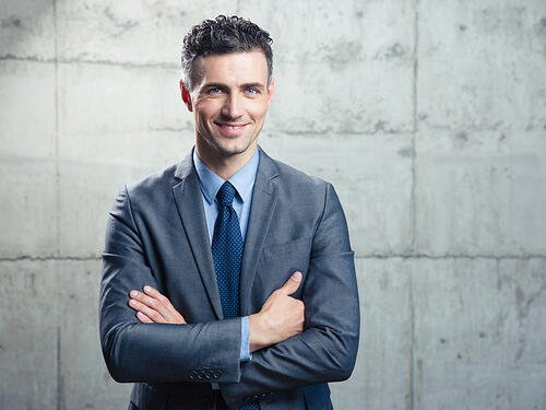 Portrait of a smiling handsome businessman with arms folded over concrete wall